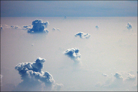 Photograph of cumulus clouds poking through a smoke layer above the Amazon.