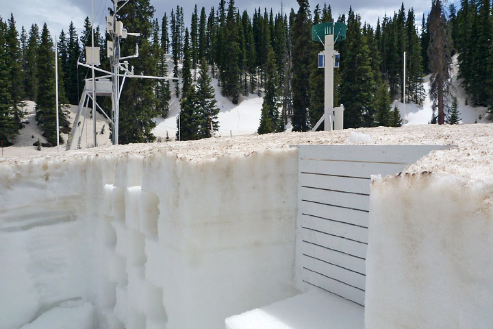 Photograph of a snow pit that reveals layers of dust in the late-season Colorado snowpack.