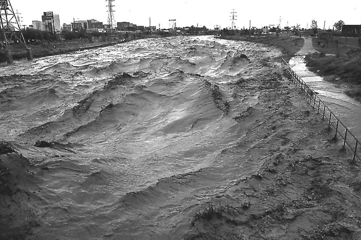 Photograph of the Santa Cruz River with strong waves and flooding.