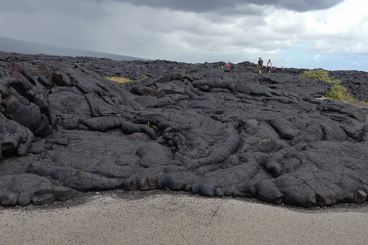 Photograph of a lava flow over an asphalt road in Volcanoes National Park, Hawaii.