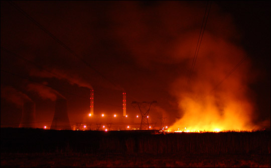 Photographs of flames from a night-time brushfire underneath South African power lines.