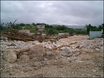This photo shows a cemetery in Jimani that was almost completely overrun by gravel and debris deposited by the torrential flows of rainwater running down the northern flank of the Massif de la Salle. (Photo by Manual Santana courtesy USAID)