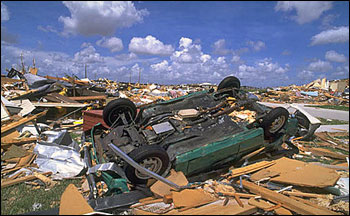 Category 5 damage: flipped car and destroyed buildings