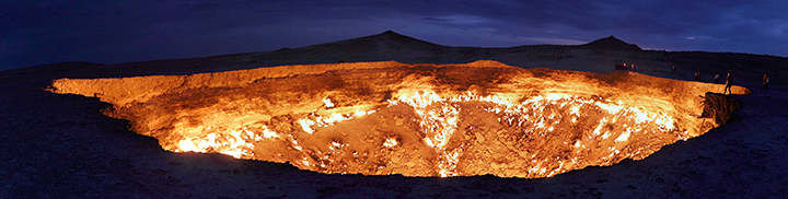 Bystanders watch as natural gas burns alongside a crater, caused by natural gas drilling.