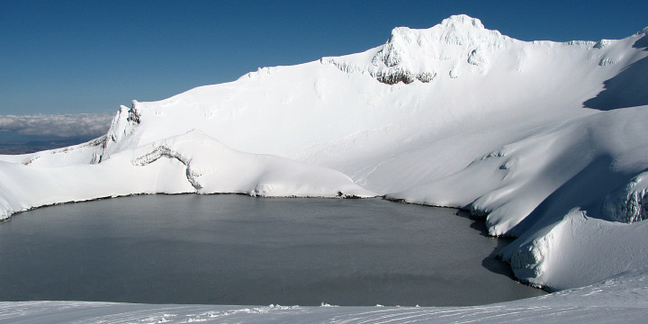 A warm, sulfurous lake lies within the snow-covered summit crater of  Mount Ruapehu, New Zealand.