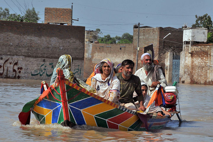 Photograph of a family escaping the floods in northwestern Pakistan by boat.