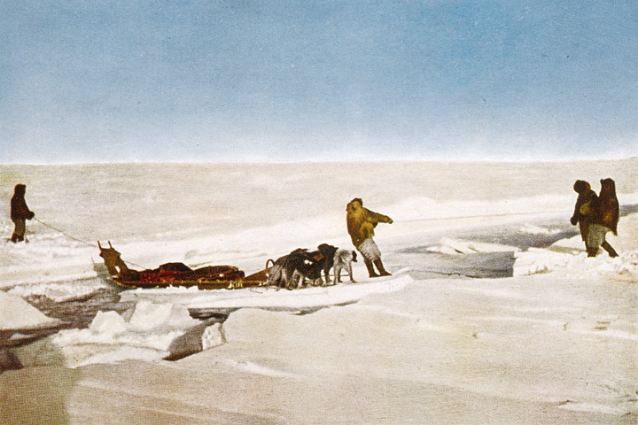 Colored photograph of members of Peary's 1909 expedition crossing an open lead on Arctic sea ice.