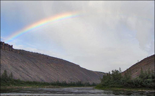 Photograph of a rainbow above the Kotuykan River, flanked by steep mountainsides.
