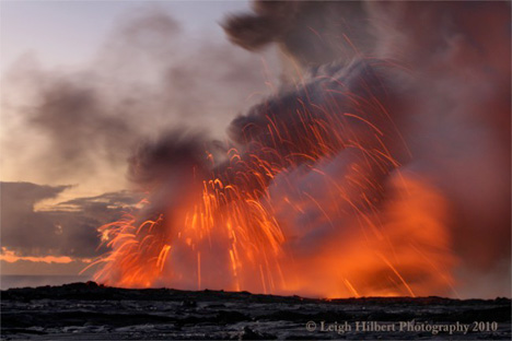 Incandescent rocks fly through the air during a lava bench collapse along the Hawaiian coast.