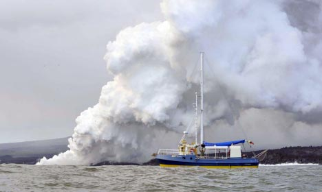 Godfrey Merlen aboard his little ship Ratty while Fernandina erupts behind him in April 2009.