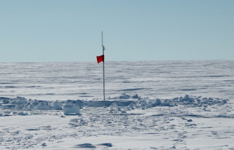After backfilling the snow pit, the only evidence at the surface of the temperature strings is the top of the pole with the ARGOS antenna and a red flag!