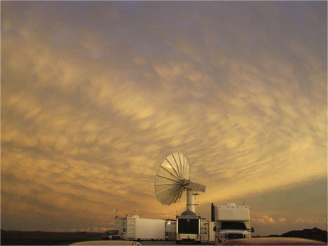 The NPOL radar against a bacground of wavy clouds at sunset.