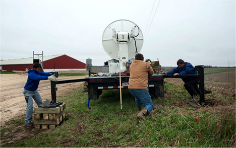 May 2, 201, St. Olaf Site:  The St. Olaf installation was a bit better, 38 degrees F (warm??) , overcast, and very windy, with rain all day. Visiting scholar Jacopo Grazioli, Dan Ceynar, and Radek Goska of the Iowa Flood Center adjust the radar position on the cribbing. Credit: Iowa Flood Center