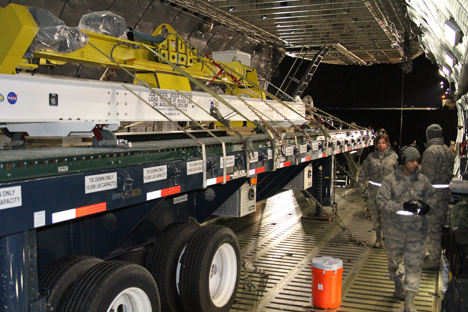 The roller bed truck loaded on the plane. Secured on top are the FlipRight (yellow) for manipulating the spacecraft once it's in the cleanroom in Japan and the I-beam sling (white) that facilitates the heavy lifting of the container. Credit: NASA / Michael Starobin