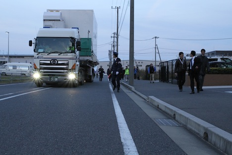 A slow-motion convoy of cars, one big truck, and lots of pedestrians walked alongside the GPM satellite about a mile from the runway at Kitakyushu Airport to the dock area. Credit: NASA / Michael Starobin