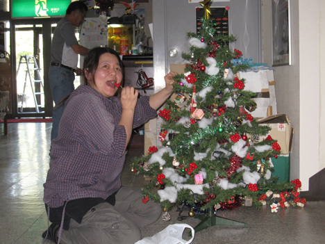 Midori Asou, one of the owners of the Sun Pearl Hotel, pretending to eat a fake holly berry while she decorates a Christmas tree. Credit: NASA / Ellen Gray