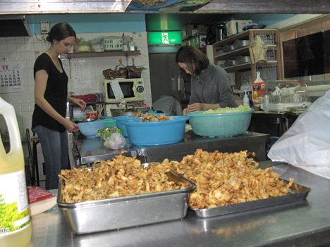 Courtney Buell and Yumiko Seki at work in the kitchen of the Sun Pearl Hotel. Credit: NASA / Ellen Gray