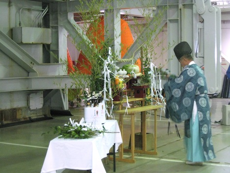 The Shinto shrine set up at the base of the rocket and the Kannushi, or priest, who led the ceremony. Jan 20. Credit: Mitsubishi Heavy Industries