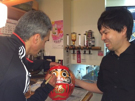 Art Azarbarzin, GPM project manager, fills in the second eye of the JAXA Daruma doll at the party after launch with JAXA engineer Hyakusoku Yasutoshi, Feb 28. Credit: Lynette Marbley
