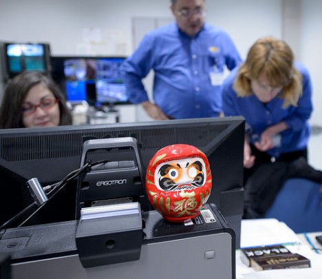 A daruma doll is seen amongst the NASA GPM Mission launch team in the Spacecraft Test and Assembly Building 2 (STA2) during the all-day launch simulation for the Global Precipitation Measurement (GPM) Core Observatory, Saturday, Feb. 22, 2014, Tanegashima Space Center (TNSC), Tanegashima Island, Japan. One eye of the daruma doll is colored in when a goal is set, in this case a successful launch of GPM, and the second eye is colored in at the completion of the goal. Credit: NASA/Bill Ingalls