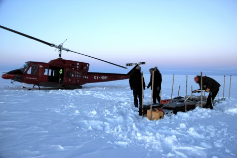 Our cargo line on the ice sheet, near the temperature probe and Argos antenna we left behind in 2013. I'm finishing up by deploying a second cargo strap across the line and through the boxes handles. (Credit: Clément Miège)