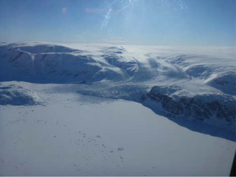 An outlet glacier draining the Greenland ice sheet into an ice covered fjord. The individual rough blocks of ice within the smooth surface of the frozen fjord are icebergs that calved off the glacier last summer and are now trapped in the winter fjord ice. (Credit: Rick Forster.)
