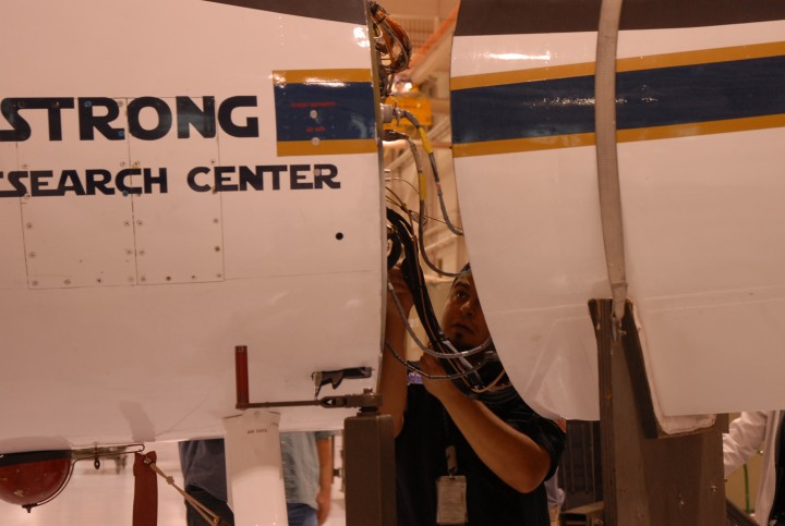 Luis Rios, with NASA's ER-2 crew, checks the connections between the MABEL instrument and the aircraft. (Credit: Kate Ramsayer/NASA)