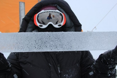 Lora with Clem reflected in goggles holding an ice core with water bubbles.