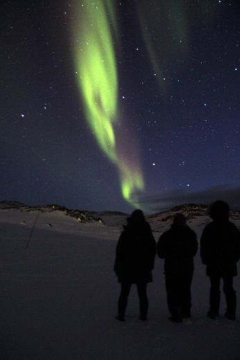 Lynn, Lora, and Olivia watching the northern lights. Photo by Clément Miège.