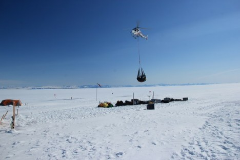 The helicopter taking in a sling load full of our gear.