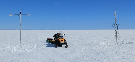 iWS standing next to the firn and water level logging station with our snowmobile in between for scale.
