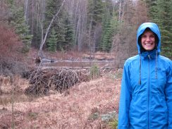 Ruthie standing next to a beaver dam. If you look behind the dam, and across the lake, on the left hand side, you can kind of see a big pile of mud and sticks – that's the beaver lodge.