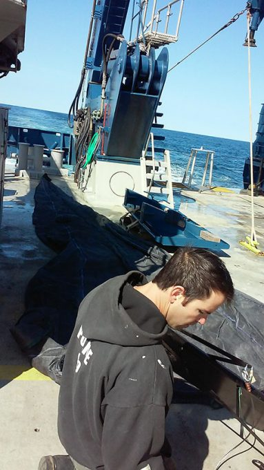 Crew member Ronnie Whims laying out the mesopelagic fish net on the aft deck of the RV Atlantis. Photo: Kelsey McBeain
