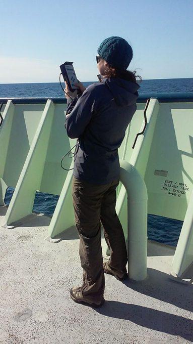 Cleo Davis measuring the amount of aerosols between the RV Atlantis and the sun, using Microtops.  Photo: Kelsey McBeain