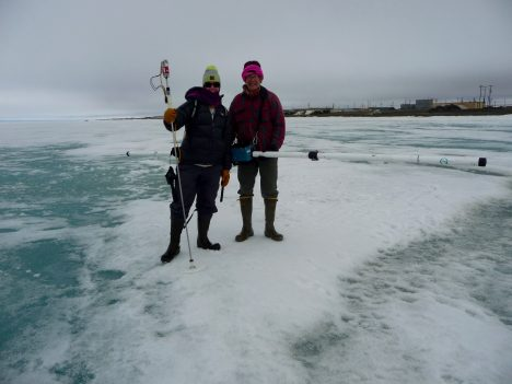 Two members of the Red Team holding the electromagnetic  induction instrument to measure sea ice thickness.