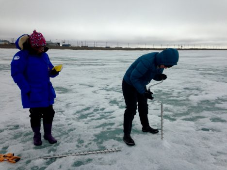 Two members of the Red team drilling with an ice auger.