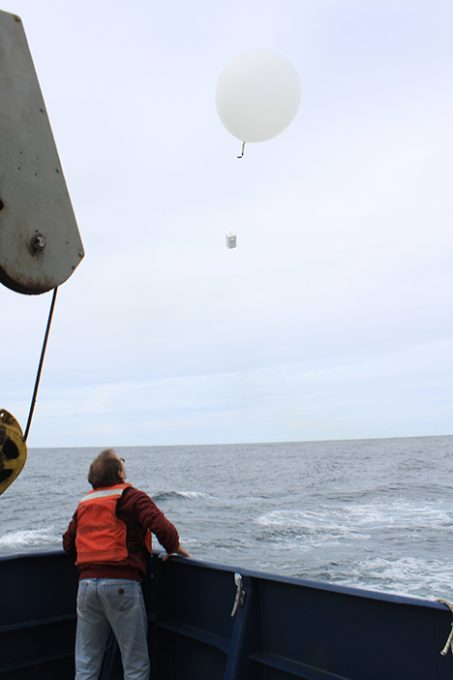 The balloon and radiosonde are walked to the back of the ship's fantail and released.  As the package rises it sends back the data by a radio link to make a vertical profile of temperature, humidity and winds. Photo: Jim Johnson