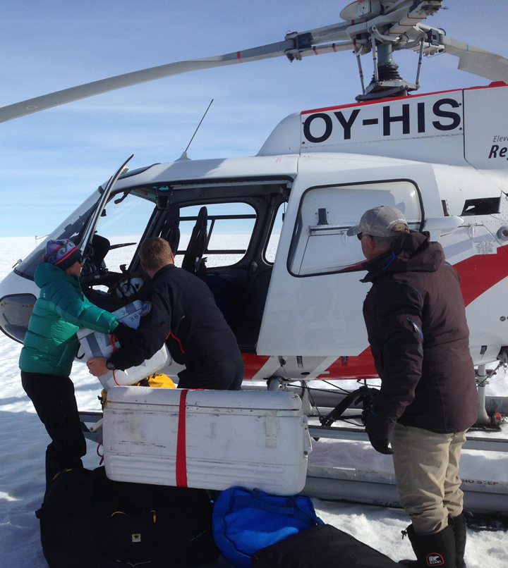 Olivia hands our precious water samples to Johannes for loading them in the helicopter as our first priority.