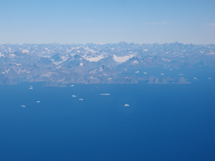 First view of the coast of East Greenland. The ocean is filled with enormous icebergs.