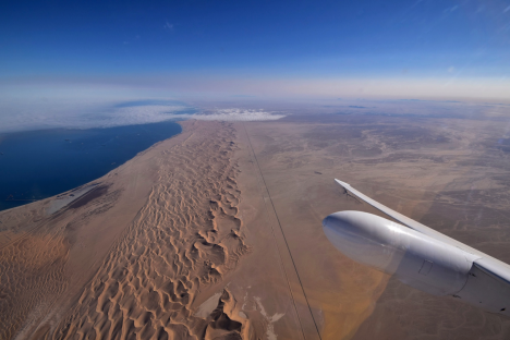 Swakopmund is under the clouds in the photo, at the end of the straight dirt road that runs 20 miles along the dunes between town and Walvis Bay Airport. Credit: Stu Broce