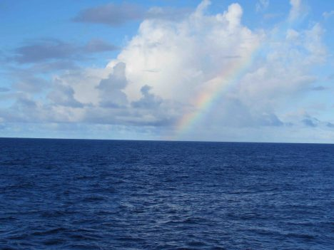 Blue sea and sky, with a nice rainbow.
